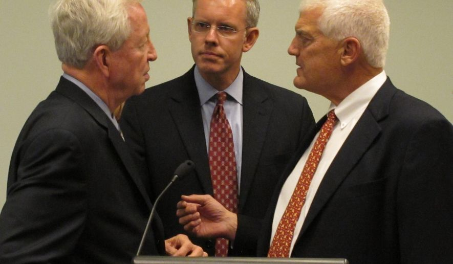 Paul Davis, center, the Democratic candidate for Kansas governor, confers with former Kansas Senate President Steve Morris, left, a Hugoton Republican, and former state Sen. Wint Winter Jr., right, a Lawrence Republican, before a news conference, Tuesday, Oct. 14, 2014, at the public library in Topeka, Kan. Morris and Winter are leaders of a group of dissident Republicans backing Davis over GOP Gov. Sam Brownback. (AP Photo/John Hanna)