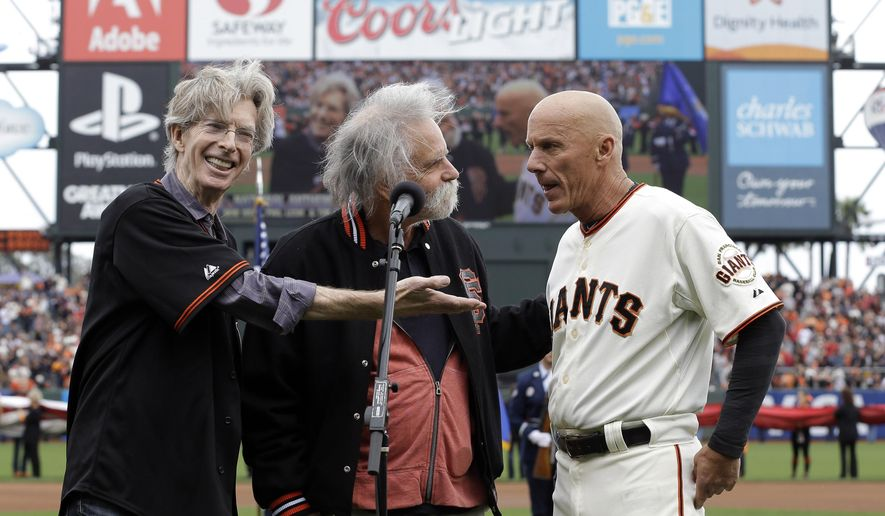 From left to right Grateful Dead's Phil Lesh, and Bob Weir with San Francisco Giants' Tim Flannery sing the national anthem before Game 3 of the National League baseball championship series between the San Francisco Giants and the St. Louis Cardinals on Tuesday, Oct. 14, 2014, in San Francisco. (AP Photo/David J. Phillip)