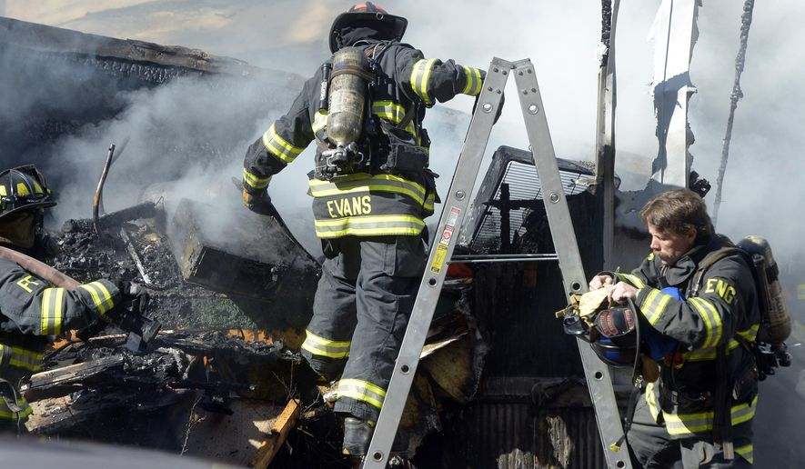 Firefighters work the scene of a fire that destroyed a home in the Boulder Meadows mobile home park in Boulder, Colo., Tuesday, Oct. 14, 2014. (AP Photo/The Boulder Daily Camera, Paul Aiken)