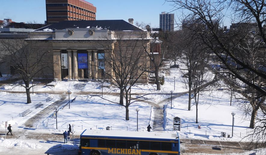 This Jan 26, 2014 photo shows a University of Michigan bus picking up students on State St. during the university's first snow day in 36 years in Ann Arbor, Mich. (AP Photo/The Ann Arbor News, Brianne Bowen)