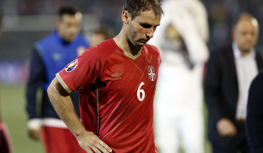 Serbia's Branislav Ivanovic bows his head while leaving the pitch during the Euro 2016 Group I qualifying match between Serbia and Albania at the Partizan stadium in Belgrade, Serbia, Tuesday, Oct. 14, 2014. The European Championship qualifier between Serbia and Albania was suspended on Tuesday after pitch skirmishes involving players and fans over an Albanian flag that was flown above the stadium by a drone. (AP Photo/Marko Drobnjakovic)