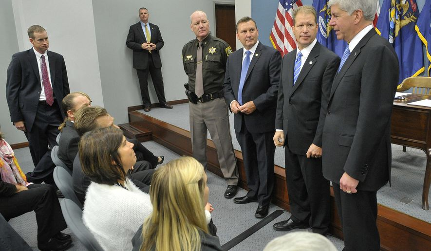 In a photo provided by the Michigan Governors Office, Michigan Gov. Rick Snyder talks with the Ward and Raymo families prior to signing bills in Lansing, Mich., Tuesday, Oct. 14, 2014 to protect motorists from repeat drugged drivers. Standing with the governor from left, are St. Clair County Sheriff Tim Donnellon, Sen. Phil Pavlov and state Rep. Dan Lauwers. The legislation allows police to conduct a preliminary roadside analysis for controlled and other intoxicating substances. (AP Photo/Michigan Governors Office, Mike Quillinan)