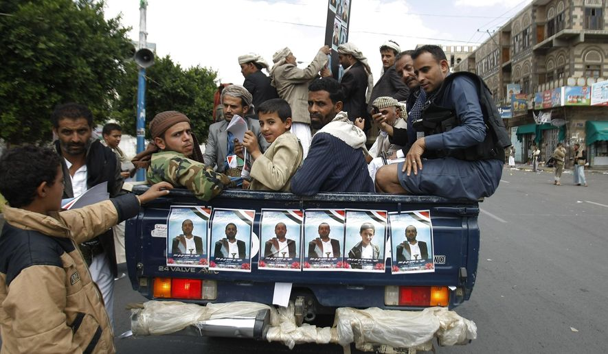 Houthi Shiite Yemenis ride on a pickup truck during funeral of victims who were killed last Thursday by a suicide bomber in central Sanaa, Yemen, Tuesday, Oct. 14, 2014. Two suicide bombings in Yemen killed nearly 70 people last Thursday, with one targeting an anti-government rally by followers of the Houthi Shiite group, who control Sanaa. (AP Photo/Hani Mohammed)