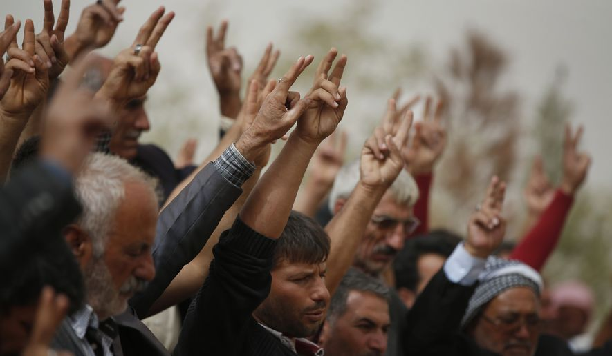 Mourners flash the victory sign as they sing a nationalistic Kurdish song at a cemetery in Suruc, Turkey, during the funeral of two Syrian Kurdish fighters. (AP Photo/Lefteris Pitarakis) ** FILE **