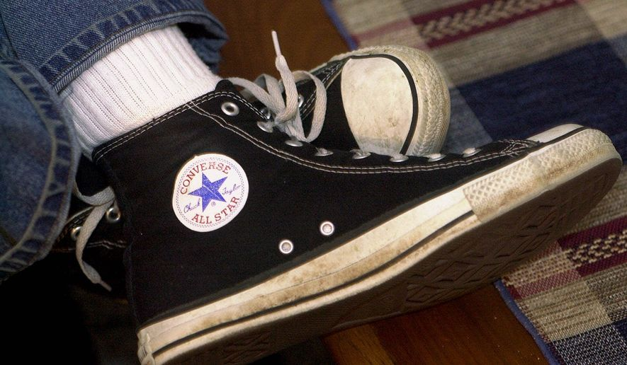 "In this March 27, 2001, file photo, Mike Costantino displays his pair of Converse ""Chuck Taylor All Star"" basketball shoes at his home in Raleigh, N.C. Converse, acquired by Nike Inc. in 2003, on Tuesday, Oct. 14, 2014 said it is suing 31 companies, saying they are selling knockoff versions of its Chuck Taylor shoes. (AP Photo/Grant Halverson)"