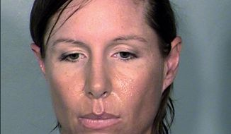 FILE - This April 11, 2014 Clark County Detention Center booking file photo provided by the Las Vegas Metropolitan Police Department shows Alison Michelle Ernst, 36, of Phoenix. A federal judge in Las Vegas dismissed a misdemeanor violence against a person charge against Ernst who pleaded guilty last month to trespassing in a shoe-throwing incident involving former U.S. Secretary of State Hillary Rodham Clinton. Ernst could face up to six months in prison but has already been in custody since shortly after the April 10 incident in which a soccer shoe missed Clinton on stage at the Mandalay Bay resort. (AP Photo/Las Vegas Metropolitan Police Department, file)