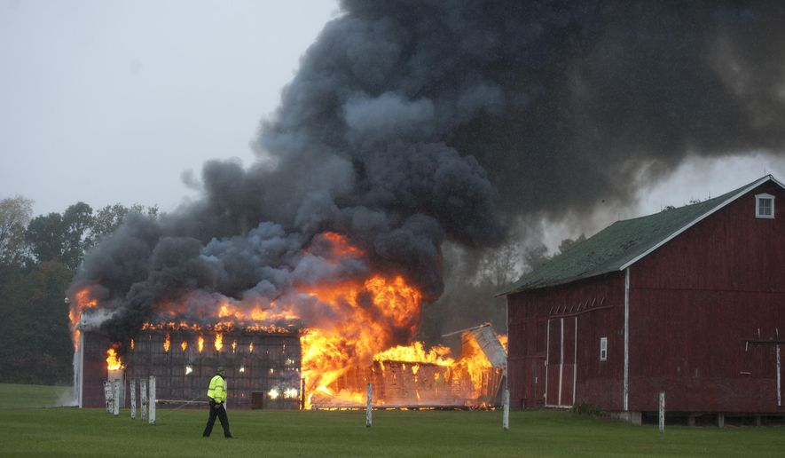 In this Monday, Oct. 13, 2014 photo, a barn and house burn on Michigan Avenue in Sandstone Township, Pa. Authorities say three students may be responsible for the fires on the Western School District property. (AP Photo/The Jackson Citizen Patriot-MLive Media, J. Scott Park) ALL LOCAL TELEVISION OUT; LOCAL TELEVISION INTERNET OUT
