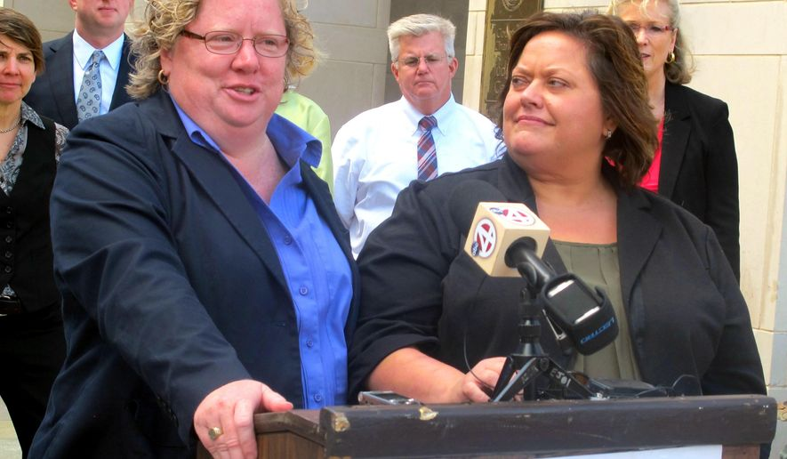 Colleen Condon, left, and her partner Nichols Bleckley appear at a news conference in Charleston, S.C., on Wednesday, Oct. 15, 2014, shortly after filing a federal lawsuit seeking the right to marry in South Carolina. Their suit is somewhat different from one before another federal judge in the state where a couple who married out of state is asking that South Carolina recognize their marriage. Condon and Bleckley applied for a marriage license on Oct. 8, 2014 in Charleston but the license was not issued. South Carolina's attorney general has asked the state Supreme Court to stop a judge from issuing marriage licenses to same-sex couples. (AP Photo/Bruce Smith)