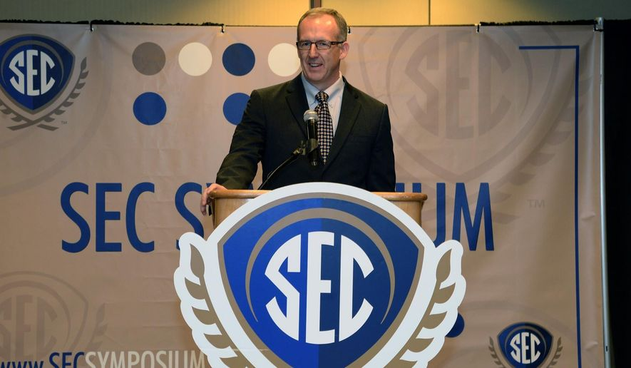 This 2014 photo provided by the Southeastern Conference shows SEC executive associate commissioner and chief operating officer Greg Sankey speaking at the SEC Symposium in Atlanta. Sankey is limping around on a knee that is feeling the effects of having completed 41 marathons, most of which he has run during the last 12 years when he has been working at the Southeastern Conference as the commissioner's right-hand man on NCAA compliance and reform.  (AP Photo/SEC)