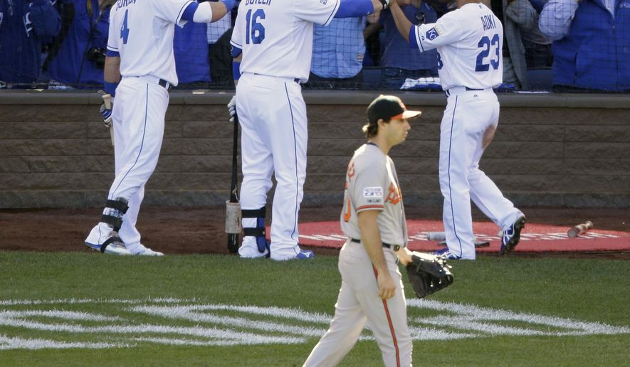 Kansas City Royals' Norichika Aoki (23) is cogradulated by Billy Butler (16) and Alex Gordon (4) after scoring as Baltimore Orioles starting pitcher Miguel Gonzalez walks back to the mound during the first inning of Game 4 of the American League baseball championship series against the Baltimore Orioles Wednesday, Oct. 15, 2014, in Kansas City, Mo. (AP Photo/Michael Conroy)