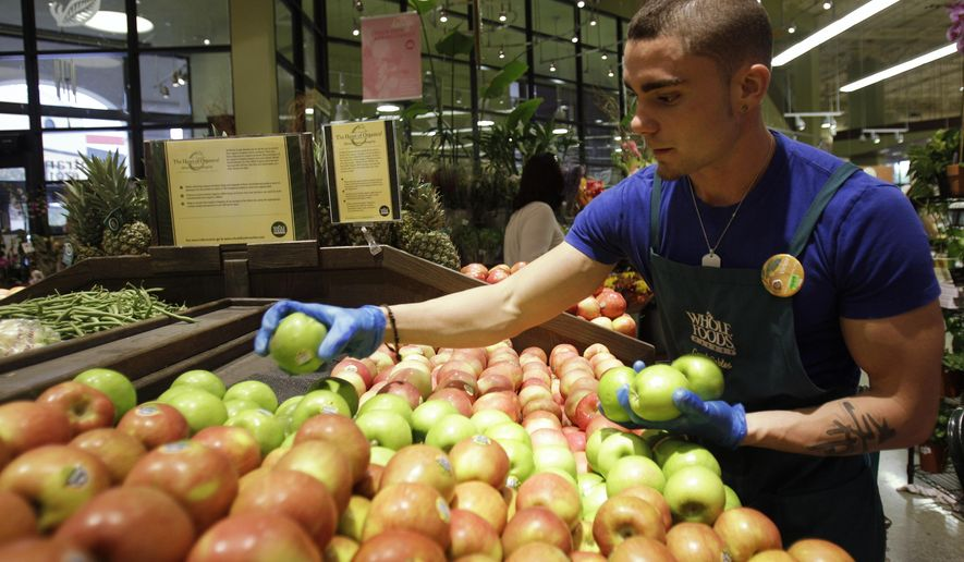 "FILE - In this Nov. 3, 2010 file photo, Victor Hernandez stocks apples in the produce section at Whole Foods, in Coral Gables, Fla. Whole Foods on Wednesday, Oct. 15, 2014 plans to start rolling out a system that ranks fruits and vegetables as ""good,"" ''better"" or ""best"" based on the supplier's farming practices. (AP Photo/Lynne Sladky, File)"