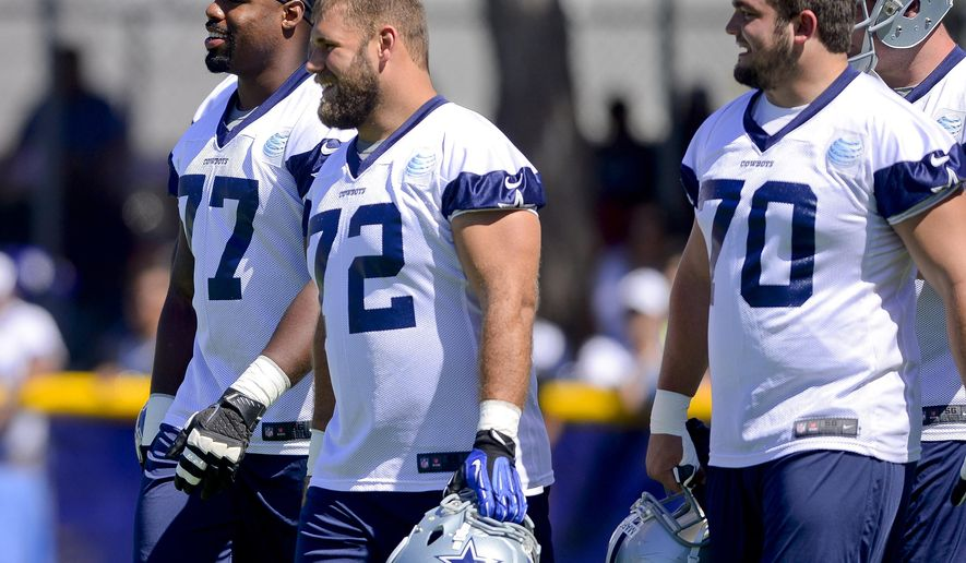 FILE - In this July 24, 2014, file photo, Dallas Cowboys offensive tackle Tyron Smith (77), center Travis Frederick (72) and guard Zack Martin (70) take the field for afternoon practice during an NFL football training camp in Oxnard, Calif. Smith, Frederick and Martin are 23-year-old first-round draft picks anchoring the Dallas offensive line for NFL rushing leader DeMarco Murray. (AP Photo/Gus Ruelas, File)