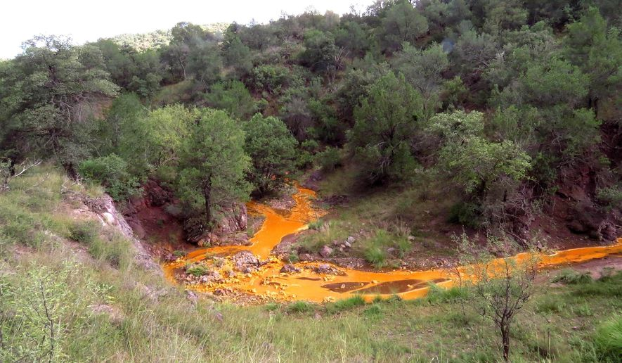 This undated photo shows orange sludge leaking from the Trench Camp Mine near Patagonia, Ariz. Heavy rain from Hurricane Odile has caused the two abandoned mines to spill orange sludge into waterways that lead to the popular Patagonia Lake in southern Arizona. (AP Photo/Arizona Republic, Gooch Goodwin)