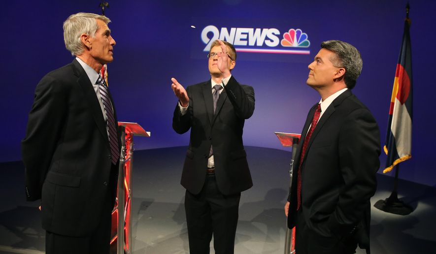Incumbent U.S. Sen. Mark Udall, D-Colo., left, and his opponent U.S. Rep. Cory Gardner, R-Colo., right, watch as 9NEWS KUSA-TV political reporter Brandon Rittiman flips a coin to determine who gets the first question, before the start of a televised debate at 9News in Denver, Wednesday Oct. 15, 2014. (AP Photo/Brennan Linsley)