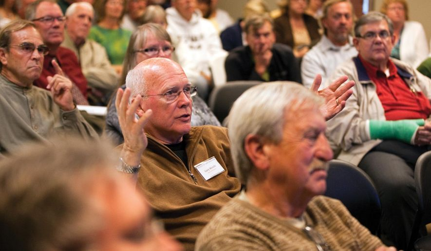 Gary Woods, center, a member of the board of directors of the Friends of Lake Manawa, asks a question for FYRA Engineering and Iowa Department of Natural Resources officials during a public forum, regarding two renovation projects on Lake Manawa State Park, at Bass Pro Shops in Council Bluffs, Iowa, Tuesday, Oct. 14, 2014. (AP Photo/The Daily Nonpareil, Joe Shearer)