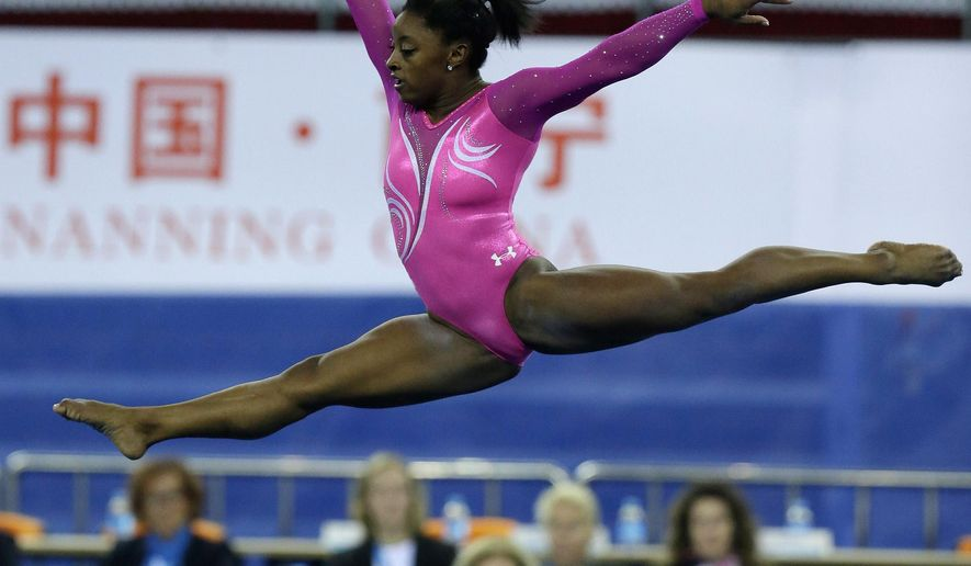 FILE - In this Oct. 5, 2014, file photo, Simone Biles of the United States performs her floor exercise during the women's qualifying of the Artistic Gymnastics World Championships at the Guangxi Gymnasium in Nanning, China. Biles won her second world all-around gymnastics last weekend in China, becoming the first U.S. woman to win two straight world all-around titles since Shannon Miller in 1993-94. (AP Photo/Andy Wong, File)