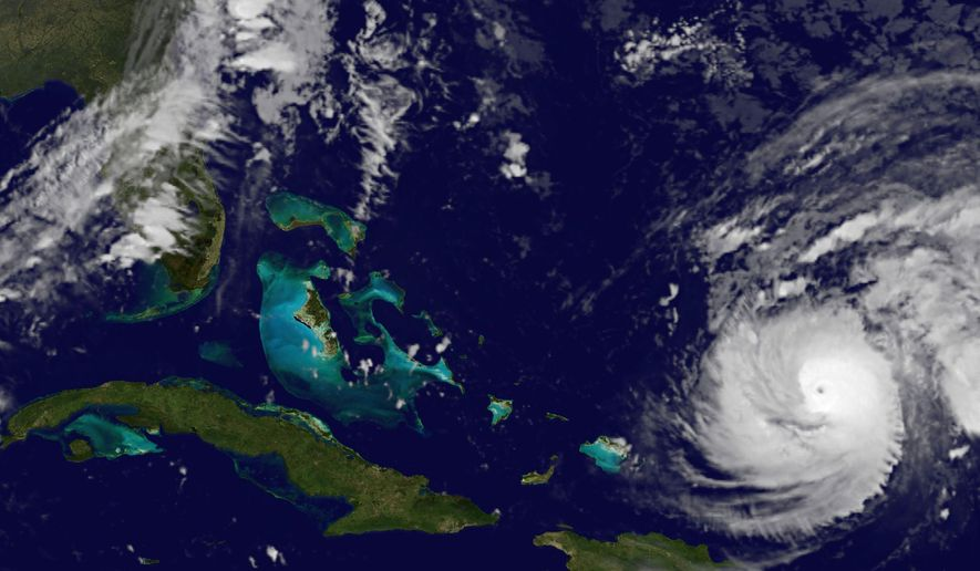 This image provided by NOAA Wednesday Oct. 15, 2014 shows Hurricane Gonzalo, lower right, which forecasters said could become a powerful category 4 storm Wednesday as it heads toward Bermuda. The storm had top sustained winds of 125 mph (205 kph) and was centered about 665 miles (1,075 kilometers) south of Bermuda early Wednesday, the U.S. National Hurricane Center said. It was moving northwest at 13 mph (20 kph). (AP Photo/NOAA)