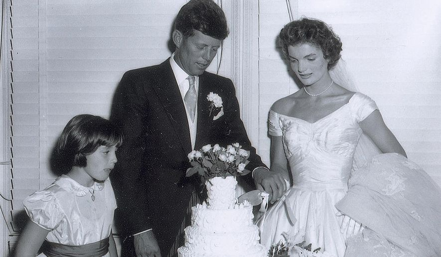 In this Sept. 12, 1953, photo released by RR Auction, John F. Kennedy and his new bride Jacqueline cut the wedding cake at their reception in Newport, R.I. The photo is one of a collection of 13 original images made by Frank Ataman, of Fall River, Mass., being auctioned by RR Auction. The original negatives were discovered in his darkroom after he died. The auction closes Wednesday, Oct. 15, 2014. The little girl is unidentified. (AP Photo/RR Auction, Frank Ataman) ** FILE **