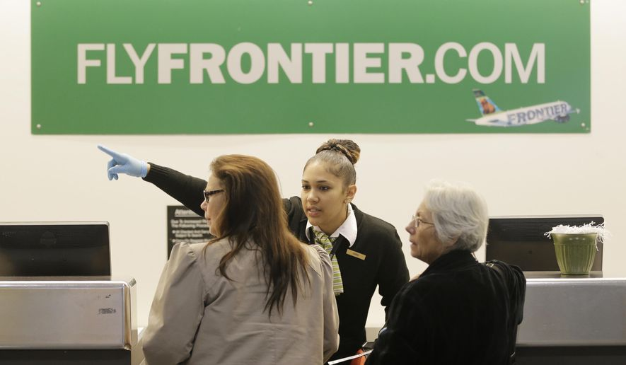 A Frontier Airlines employee wears rubber gloves as she directs passengers where to go at Cleveland Hopkins International Airport Wednesday, Oct. 15, 2014, in Cleveland. Ohio health officials aren't sure how many people came into contact with a Texas nurse as she visited family in the Akron area days before being diagnosed with Ebola in Dallas. The Ohio Department of Health says she visited family from Oct. 8-13 and flew Monday from Cleveland to Dallas. (AP Photo/Tony Dejak)
