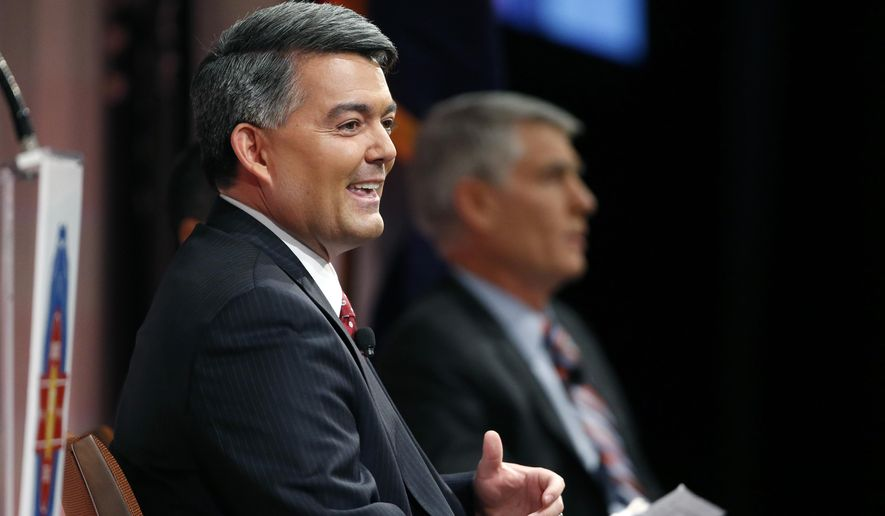 In this Oct. 6, 2014 photo, candidate for U.S. Senate, Rep. Cory Gardner, (R-Colo.), left, speaks as incumbent U.S. Sen. Mark Udall, (D-Colo.), right, listens during a debate in Denver. The two are locked in what many polls say is a tight race, less than three weeks before election day on Nov. 4, 2014. (AP Photo/Brennan Linsley)