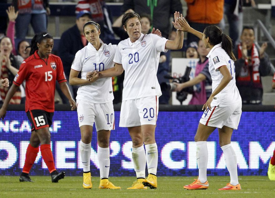 United States' Abby Wambach (20) is congratulated by teammates Carli Lloyd (10) and Christen Press (14) after scoring a goal as Trinidad and Tobago's Liana Hinds (15) walks behind during the second half of a CONCACAF Women's Championship soccer matchWednesday, Oct. 15, 2014, in Kansas City, Kan. (AP Photo/Colin E. Braley)