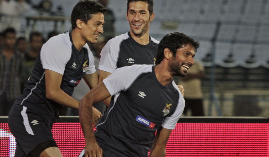 Spanish soccer star Luis Garcia, center, shares a light moment with teammates Denzil Franco, right, and Sanju Pradhan of the Atletico De Kolkata football club of the Indian Super League (ISL) during a practice session in Kolkata, India, Friday, Oct. 10, 2014. The Indian Super League begins from October 12. (AP Photo/ Bikas Das)