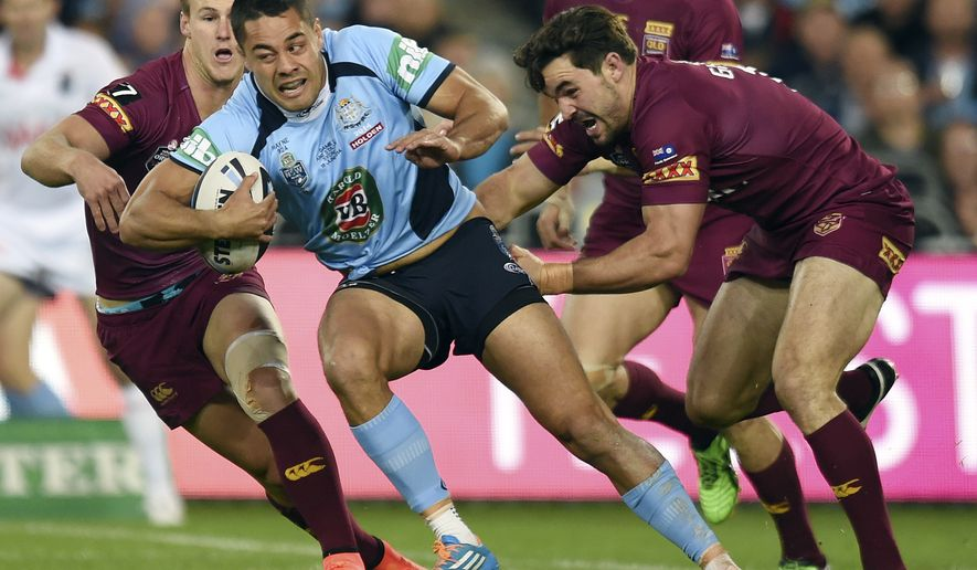 In this June 18, 2014 photo, Jarryd Hayne, center, escapes a tackle during a State of Origin rugby league series game in Sydney, Australia. Hayne stunned the rugby league world by quitting his long-time Australian club suddenly Wednesday, Oct. 15, 2014, to chase a dream of playing in the National Football League. (AAP Image/Paul Miller) NO ARCHIVING, EDITORIAL USE ONLY, AUSTRALIA OUT, NEW ZEALAND OUT, PAPUA NEW GUINEA OUT, SOUTH PACIFIC OUT