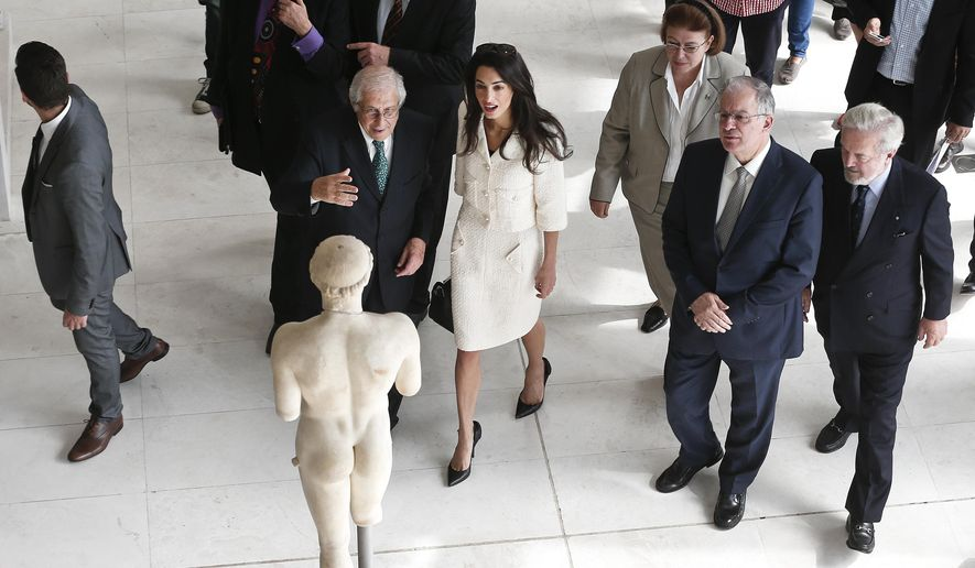 Lawyer Amal Clooney, center, is guided by the Director of the Acropolis museum Dimitris Pantermalis, left, during a visit at the Parthenon hall inside the Acropolis museum in Athens Wednesday Oct. 15, 2014. Lawyers Geoffrey Robertson, Norman Palmer and Amal Clooney arrived Monday to Greece on a four-day visit to meet government officials, including Prime Minister Antonis Samaras, and advise on Greece's quest to have the Parthenon Marbles returned to Athens. (AP Photo/Yorgos Karahalis, Pool)