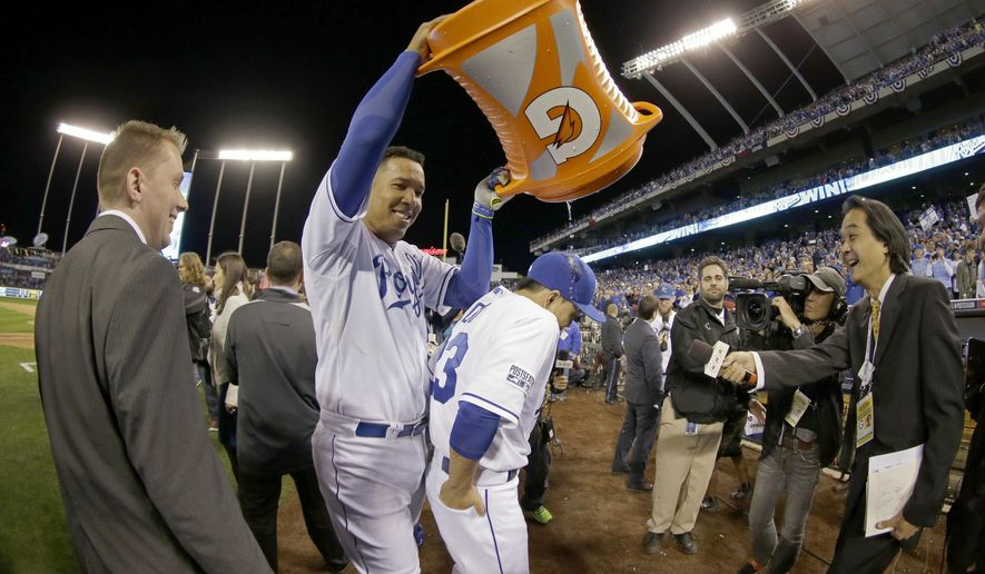 Kansas City Royals' Salvador Perez dumps water on Norichika Aoki following Game 3 of the American League baseball championship series Tuesday, Oct. 14, 2014, in Kansas City, Mo. The Royals won 2-1 and lead the series 3-0. (AP Photo/Charlie Riedel)