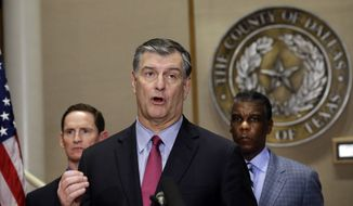 Dallas Mayor Mike Rawlings, center, speaks as Dallas County Judge Clay Jenkins, left, and Zachary Thompson, the director of Dallas County Health and Human Services, look on during a news conference announcing a second Ebola infection of a health care worker, Wednesday, Oct. 15, 2014, in Dallas. (AP Photo/LM Otero)