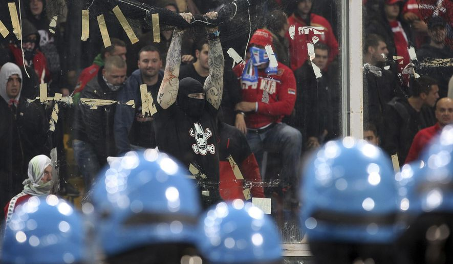 FILE - This is a Tuesday, Oct. 12, 2010 file photo of Serbia fans as they challenge Italian police prior to the start of a Group C, Euro 2012 qualifying soccer match between Italy and Serbia, at the Luigi Ferraris stadium in Genoa, Italy. The start of the Italy-Serbia European Championship qualifier has been delayed due to Serbia fans throwing flares onto the pitch and lighting fireworks. The match was later abandon due to crowd troubl.  (AP Photo/Carlo Baroncini, File)