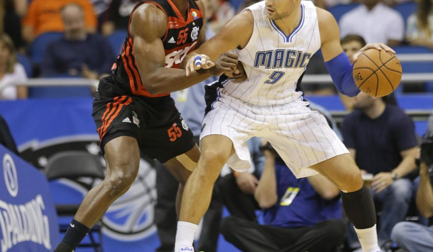 Orlando Magic's Nikola Vucevic (9) looks for a way past Flamengo Brazil's Jerome Meyinsse (55) during the first half of an NBA preseason exhibition basketball game in Orlando, Fla., Wednesday, Oct. 15, 2014. (AP Photo/John Raoux)