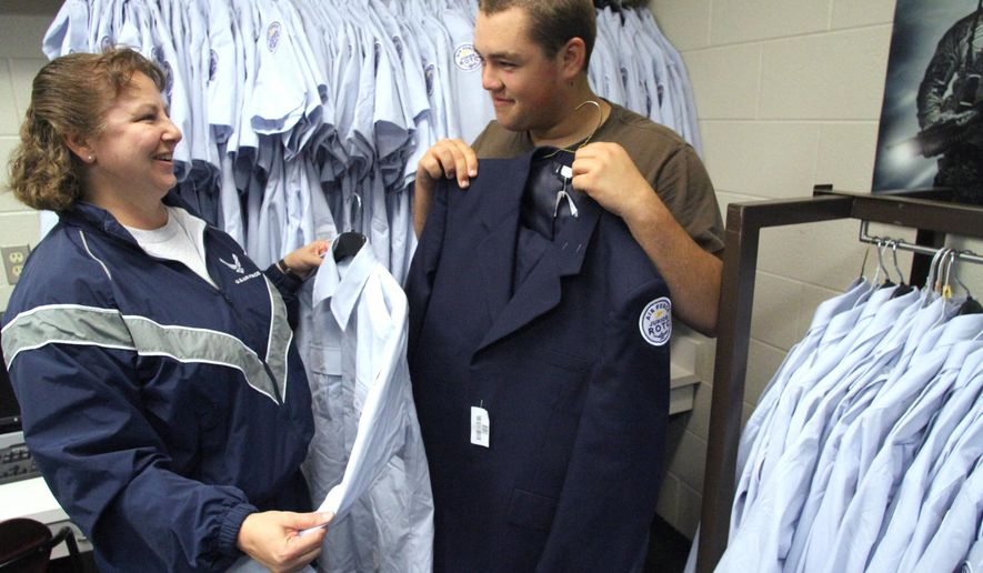 Lt Col. Sarah Scullion, left, and  Cadet Matthew Hill, right shown in the room where cadet uniforms await alterations for the newly started Junior ROTC program at Howell High School in Howell, Mich., on Sept 19, 2014. (AP Photo/Daily Press & Argus, Alan Ward)