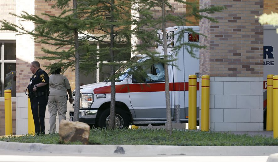 The driver of an ambulance wears protective clothing while transporting a healthcare worker who contracted Ebola to a Dallas airport for a chartered flight to Emory Hospital in Atlanta for treatment, Wednesday, Oct. 15, 2014. Emory and three other U.S. hospitals have specialized isolation units to care for Ebola with less risk of spread to health care workers. (AP Photo/Brandon Wade)