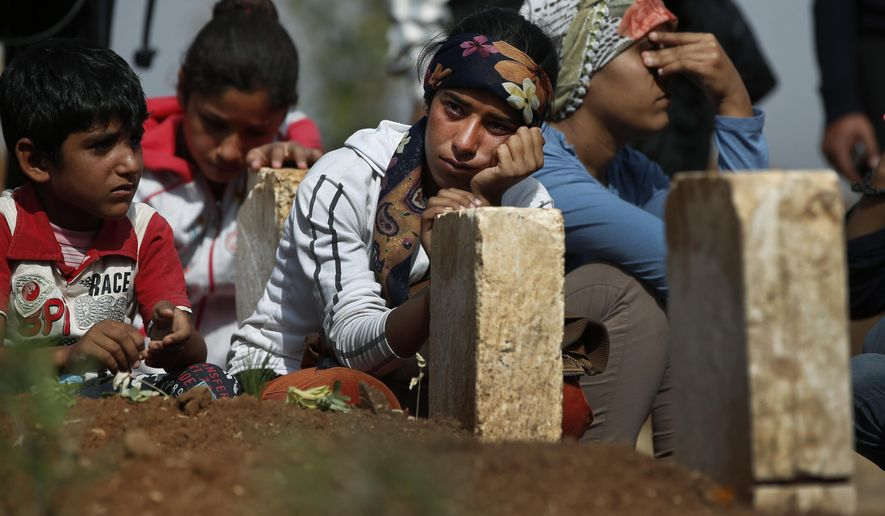 Kurdish people sit by the grave as they mourn their loved one, a Kurdish fighter, name not given, who was killed in the fighting with the militants of the Islamic State group in Kobani, Syria, and was buried at a cemetery in Suruc, on the Turkey-Syria border, Tuesday, Oct. 14, 2014. Kobani, also known as Ayn Arab, and its surrounding areas, has been under assault by extremists of the Islamic State group since mid-September and is being defended by Kurdish  fighters. (AP Photo/Lefteris Pitarakis)