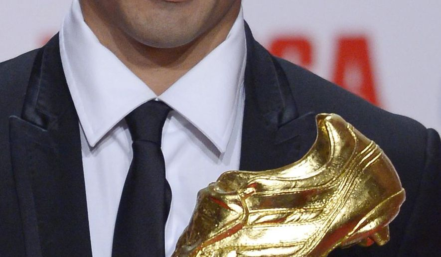 FC Barcelona's Luis Suarez, from Uruguay, poses to the media after receiving the Golden Boot award for scoring the most goals in Europe's domestic leagues last season shared with Cristiano Ronaldo in Barcelona, Spain, Wednesday, Oct. 15, 2014. (AP Photo/Manu Fernandez)