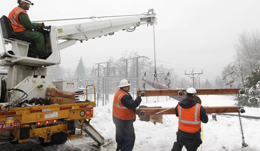 FILE - In this Jan. 20, 2012, file photo, workers on a crew for Puget Sound Energy move a new power pole into place to replace one that fell down after a tree covered in ice fell on a transmission line near a substation in Olympia, Wash. Puget Sound Energy said said Wednesday, Oct. 15, 2014 that it plans to install four shipping containers housing lithium iron phosphate batteries to keep the power on when lines go down in the Cascade mountains (AP Photo/Ted S. Warren, File)