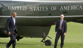 President Barack Obama walks from Marine One on the South Lawn of the White House in Washington, Tuesday, Oct. 14, 2014, upon his return from a meeting at Andrews Air Force Base, Md. The president met with military chiefs in a show of strength against Islamic State fighters in Iraq and Syria. (AP Photo/Jacquelyn Martin)