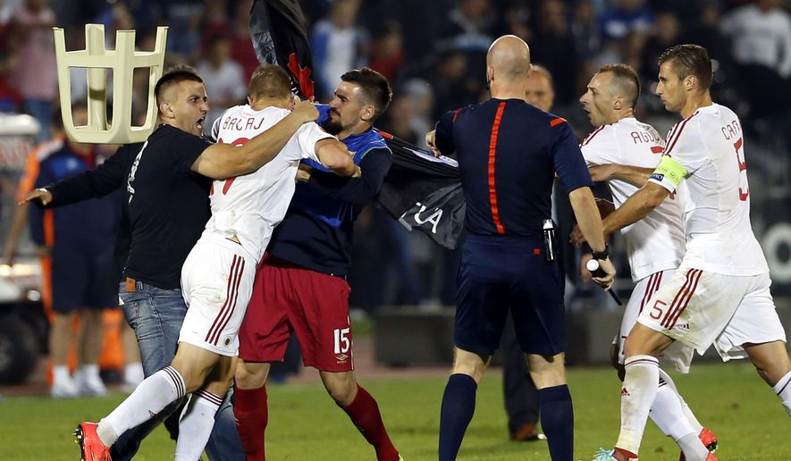 A fight breaks out on the pitch between Serbian fans and Albanian national team players, with from right, Albania's Lorik Cana, Albania's Ansi Agolli, match official, 3rd left Serbia's Nenad Tomovic holding Albanian flag, Albania's Bekim Balaj, and soccer fan at left, during the Euro 2016 Group I qualifying match between Serbia and Albania, at the Partizan stadium in Belgrade, Serbia, Tuesday, Oct. 14, 2014.  The match was suspended on Tuesday after pitch skirmishes involving players and fans over an Albanian flag that was flown above the stadium by a drone.  The score was 0-0 at the time. (AP Photo/Marko Drobnjakovic)