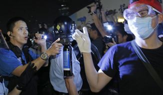 A police officer, left,  points a pepper spray can to a protester after a clash between protesters and police near a occupied area in Hong Kong early Thursday, Oct. 16, 2014. Riot police moving against activists sparked outrage after officers were seen kicking a handcuffed protester and dragging dozens of others away Wednesday in the worst violence against the pro-democracy demonstrations in Hong Kong since they began more than two weeks ago. (AP Photo/Vincent Yu)