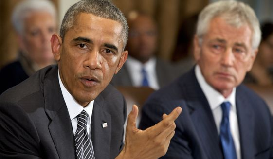 President Obama, seated next to Secretary of Defense Chuck Hagel, speaks to the media about Ebola during a meeting in the Cabinet Room of the White House on Oct. 15, 2014. (AP Photo/Jacquelyn Martin)