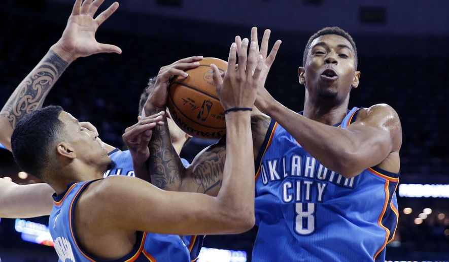 Oklahoma City Thunder forward Richard Solomon (8) and guard Andre Roberson battle for a loose ball under the basket in the first half of an NBA preseason basketball game against the New Orleans Pelicans in New Orleans, Thursday, Oct. 16, 2014. (AP Photo/Gerald Herbert)