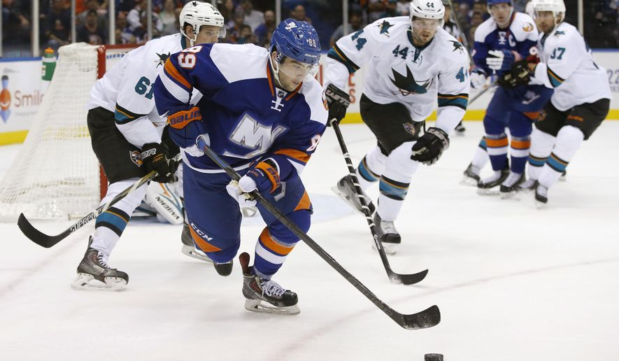 New York Islanders left wing Cory Conacher (89) moves the puck away from San Jose Sharks defensemen Justin Braun (61) and Marc-Edouard Vlasic (44) in the second period of an NHL hockey game in Uniondale, N.Y., Thursday, Oct. 16, 2014. (AP Photo/Kathy Willens)