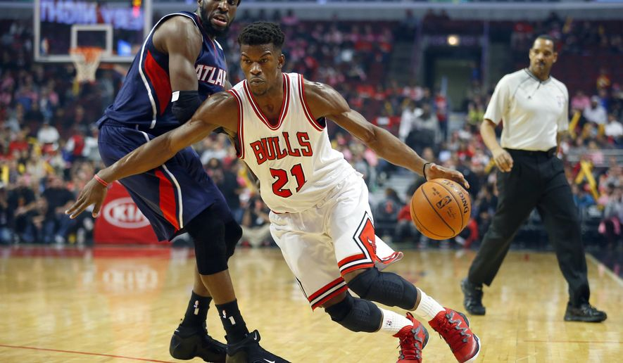 Chicago Bulls guard Jimmy Butler (21) gets past Atlanta Hawks forward DeMarre Carroll during the first half of a preseason NBA basketball game in Chicago, on Thursday, Oct. 16, 2014. (AP Photo/Jeff Haynes)