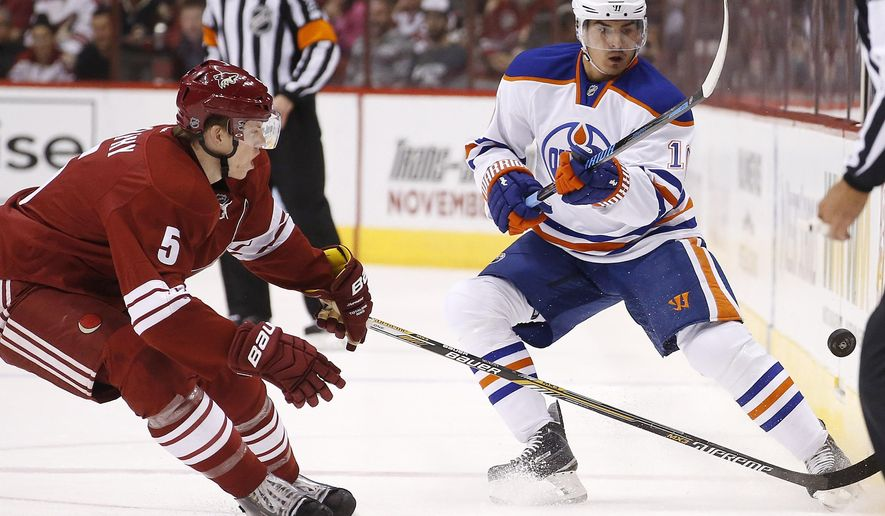 Edmonton Oilers' Nail Yakupov, right, of Russia, passes the puck as Arizona Coyotes' Connor Murphy (5) arrives to defend during the first period of an NHL hockey game Wednesday, Oct. 15, 2014, in Glendale, Ariz. (AP Photo/Ross D. Franklin)