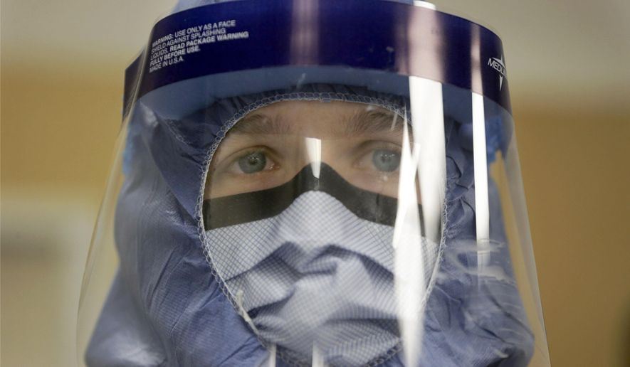 Registered nurse Keene Roadman, stands fully dressed in personal protective equipment during a training class at the Rush University Medical Center, Thursday, Oct. 16, 2014, in Chicago. With hospital workers increasingly in the spotlight of concern over the spread of the Ebola virus, the hospital held a training session for a team of medical professionals with expertise in intensive care and infection control. (AP Photo/Charles Rex Arbogast)