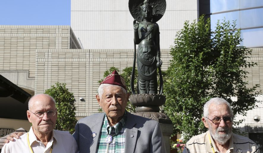 U.S. veterans, William Sanchez, center, 96, of Monterey Park, CA., Oral C. Nichols, left, 93, of Carlsbad, NM., and Jack Schwartz,  99, of Hanford, CA, stand together in front of Heiwajima Kannon by the Heiwajima Motorboat Race stand, the former site of Omori camp, where Sanchez was held before going back to the United States, in Tokyo Thursday, Oct. 16, 2014. The three former POWs are among seven invited by a Japanese government friendship program that has brought five groups of World War II prisoner of war survivors, almost all of them in their 90s, to visit the camps where they were held nearly 70 years ago during the war and speak about their experiences. (AP Photo/Koji Sasahara)
