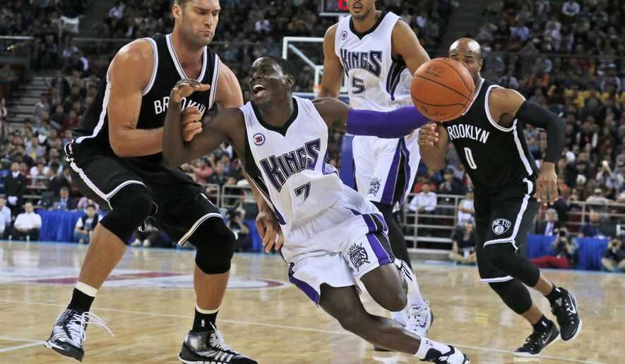 Sacramento Kings' Darren Collison, center, tries to pass Brooklyn Nets' Brook Lopez, left, during a pre-season match held in Beijing, China, Wednesday, Oct. 15, 2014. Brooklyn Nets won 129-117. (AP Photo/Ng Han Guan)
