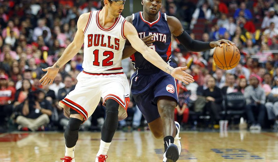 Chicago Bulls guard Kirk Hinrich (12) guards Atlanta Hawks guard Shelvin Mack (8) during the second half of a preseason NBA basketball game in Chicago on Thursday, Oct. 16, 2014. The Bulls won 85-84. (AP Photo/Jeff Haynes)
