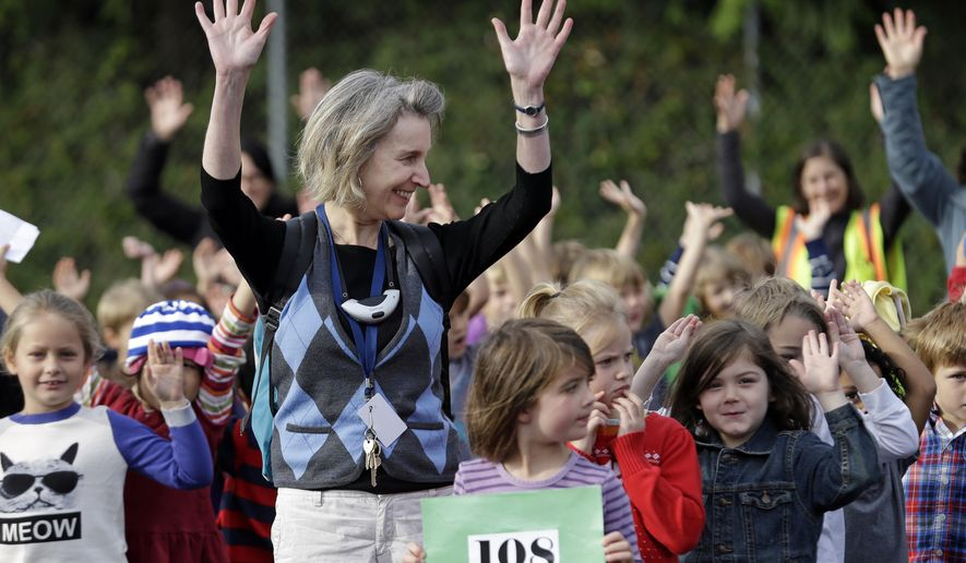 "Kindergarten teacher Theresa Healey raises her hands as she joins in cheering with students after the school was successfully evacuated to the playground during the Great Washington Shakeout drill at West Woodland Elementary School Thursday, Oct. 16, 2014, in Seattle. Thousands of students across the state practiced ducking under the desks Thursday in the coordinated drill. Shakeout organizers said more than one million people in Washington registered to participate at 10:16 a.m. on 10-16. It was part of a worldwide campaign to practice ""drop, cover and hold."" (AP Photo/Elaine Thompson)"